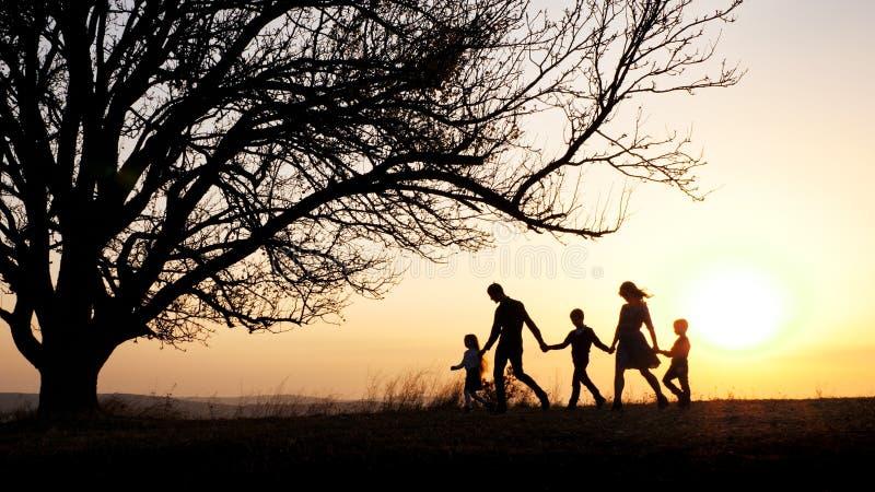 Sylwetki szczęśliwy rodzinny odprowadzenie wpólnie w łące podczas zmierzchu obraz royalty free