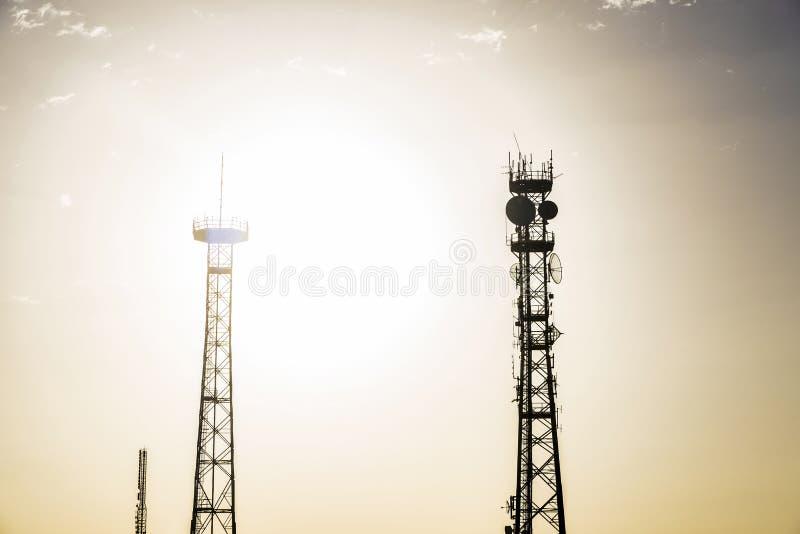 Sylwetki telekomunikacje górują przy zmierzchem zdjęcia stock