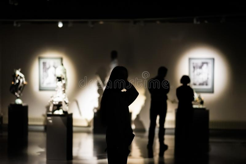 Sylwetki unrecognizable ludzie, goście galeria sztuki, muzeum z obrazami, selekcyjna ostrość zdjęcia royalty free