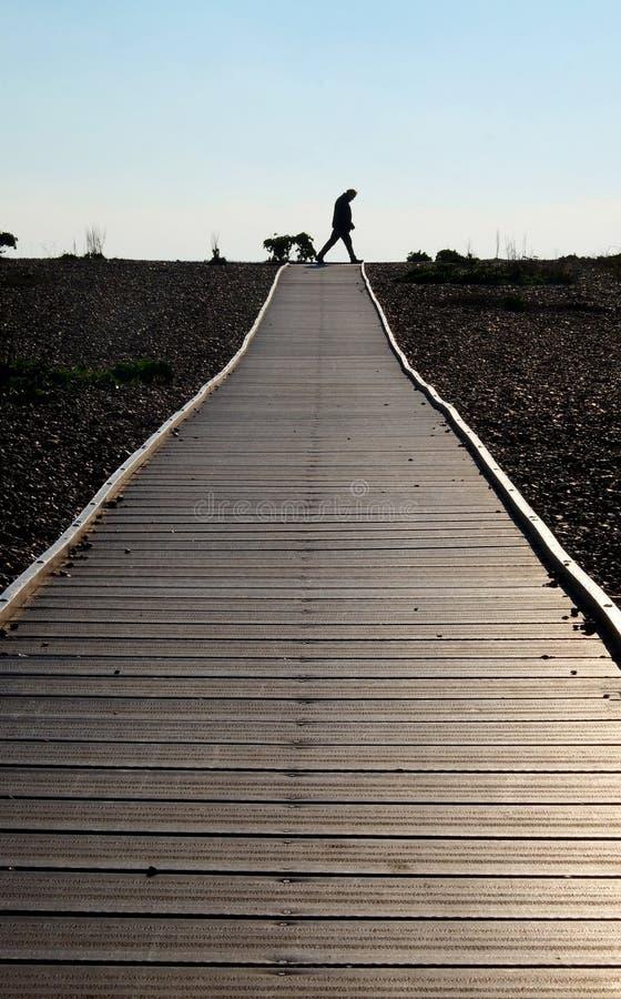 Sylwetkowi sześćdziesiąt roczniaka mężczyzny odprowadzeń przez końcówkę drewniany droga przemian zdjęcie stock