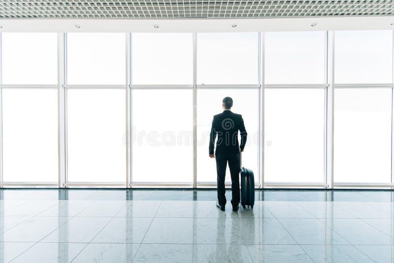 Sylwetkowy tylni widoku wizerunek biznesmen patrzeje przez okno przy lotniskiem z bagażem obrazy royalty free