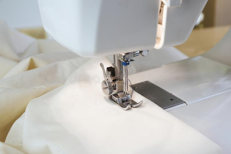 Symaskin med vitt tyg under visaren och pressen arkivbilder