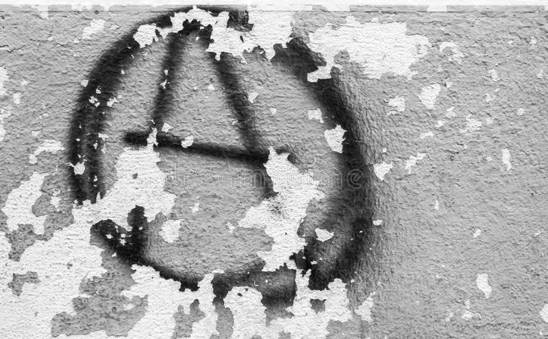Symbol of anarchy painted on the peeling old wall stock image