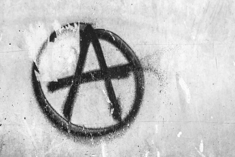 Symbol av anarki som m?las p? den skalande gamla v?ggen royaltyfri fotografi