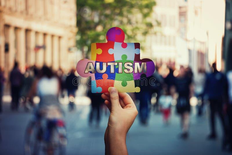 Symbol av autism som en barnhand som rymmer ett färgrikt pusselstycke över en fullsatt gatabakgrund arkivfoton