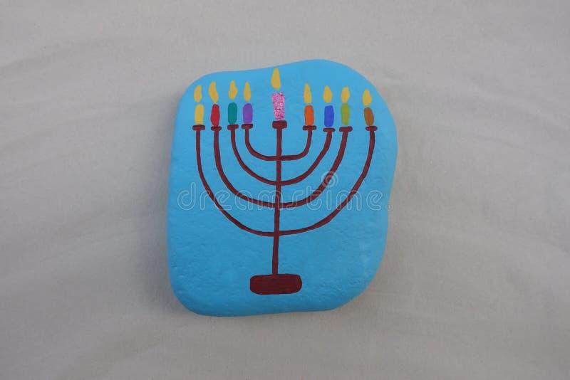 Symbol av den judiska ferieChanukkah med en målad stiliserad design av en menora, ljusstake med nio stearinljus över en sten fotografering för bildbyråer