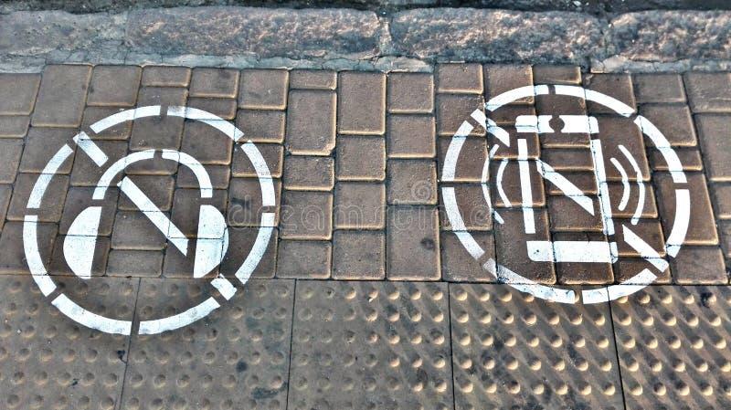 Symbol av förbud som ser mobiltelefonen och att lyssna till musik med hörlurar, medan korsa vägen royaltyfri foto