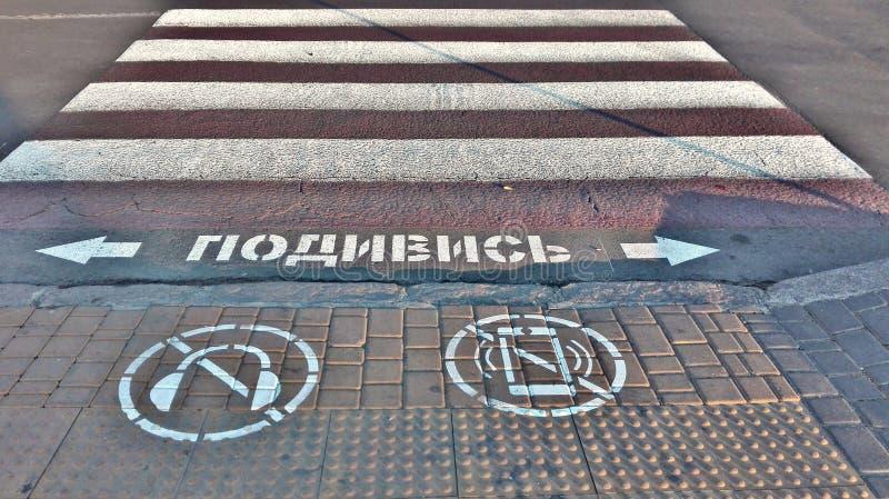 Symbol av förbud som ser mobiltelefonen och att lyssna till musik med hörlurar, medan korsa vägen arkivfoton