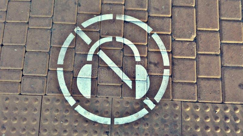 Symbol av förbud till att lyssna till musik med hörlurar, medan korsa vägen royaltyfria bilder