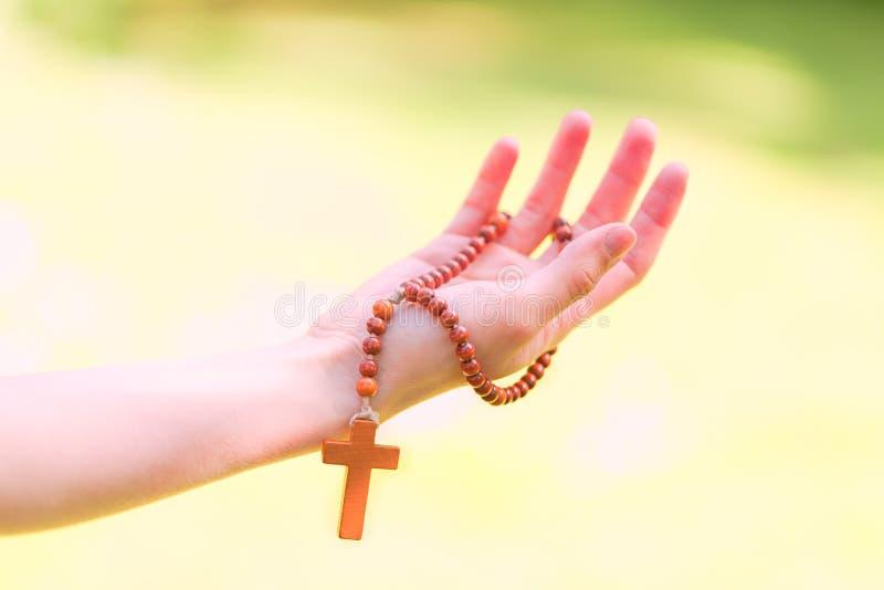 Symbol av kristendomen, träradband i händer royaltyfri fotografi