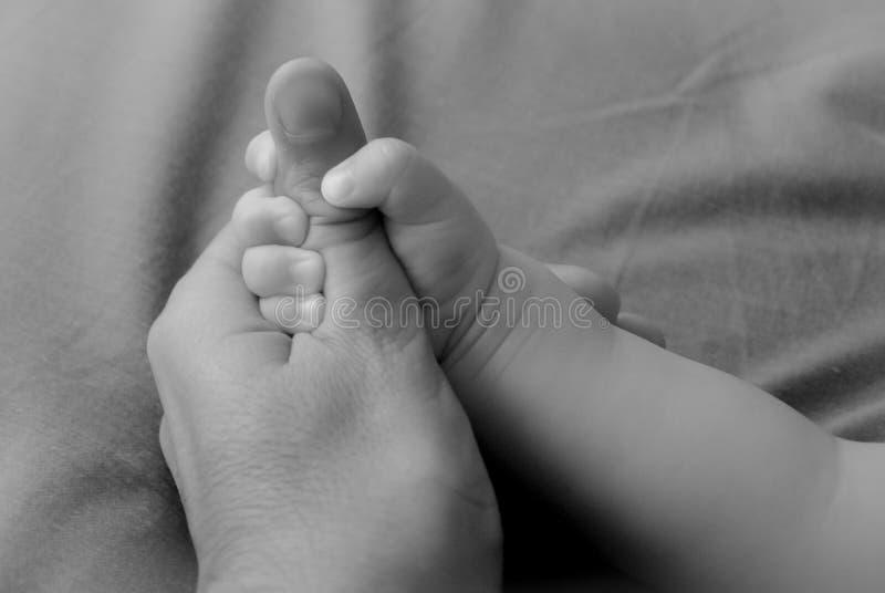 Symbol av union mellan fadern och sonen Barnet rymmer tummen av fadern med hans hand royaltyfri foto