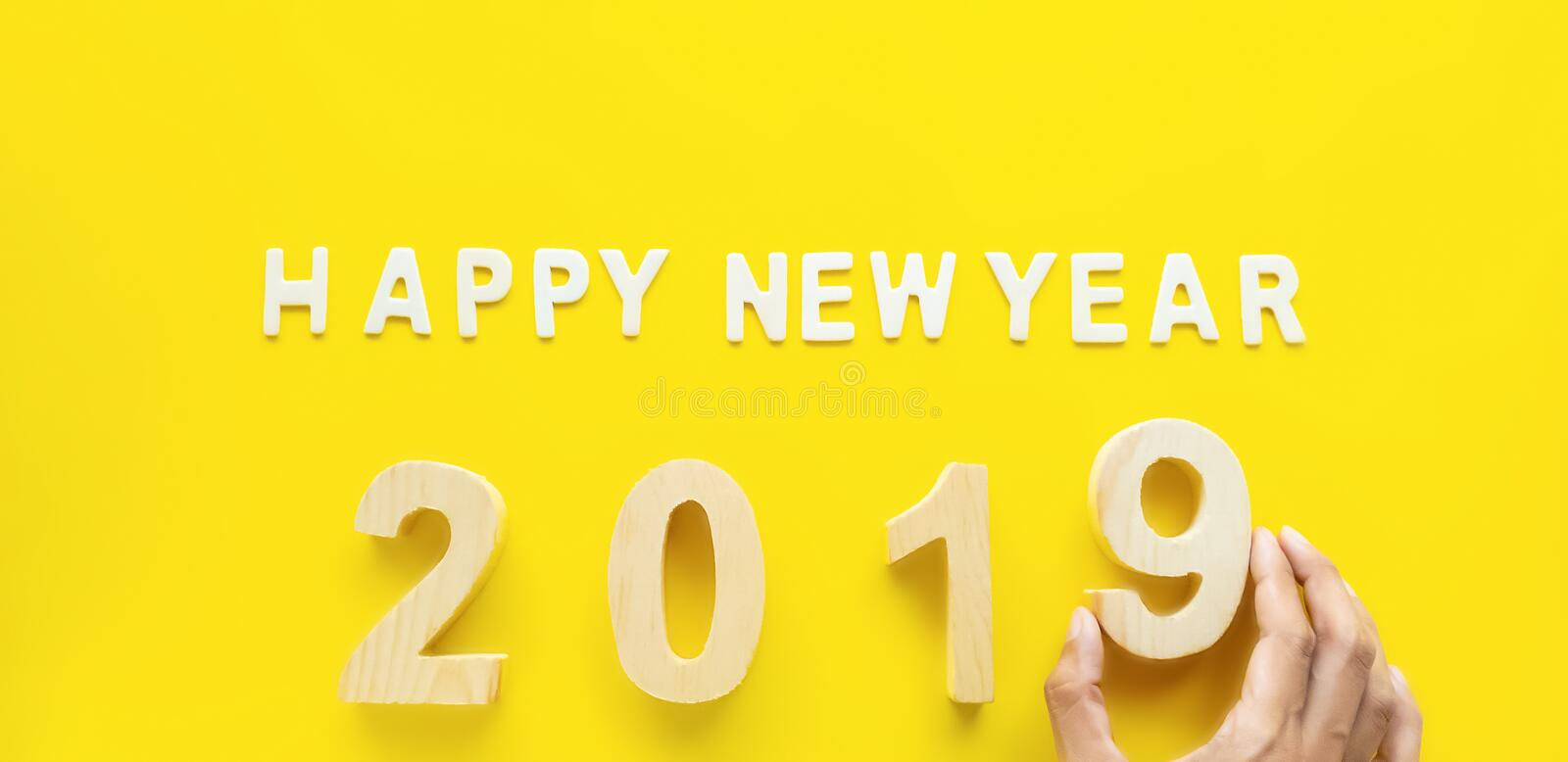 Symbol Celebration for 2019 year, wooden text Happy new Year 2019 on bright yellow paper background .Holiday Concept royalty free stock photography