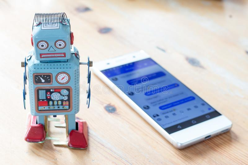 Symbol for chat bot, smartphone and messenger. Toy robot and smartphone, symbol for chatbot and messenger surveillance social algorithm artificial code stock photo