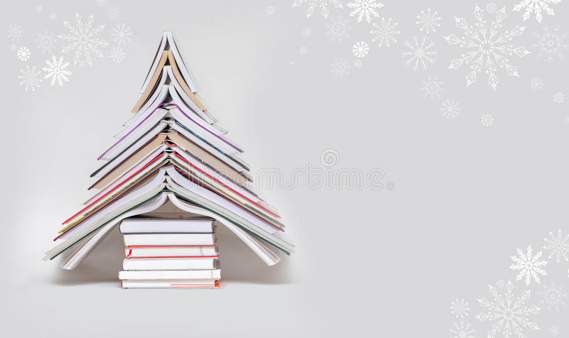 Symbol Christmas tree from a colorful books on grey background. stock image