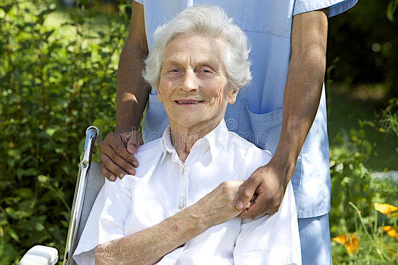 Symbol of comfort and support from a care giver to the Senior. Symbol of comfort and support from care giver to smiling elderly women outdoor stock images