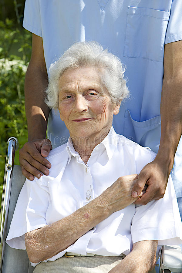 Symbol of comfort and support from a care giver to the Senior. Symbol of comfort and support from care giver to smiling elderly women outdoor royalty free stock images