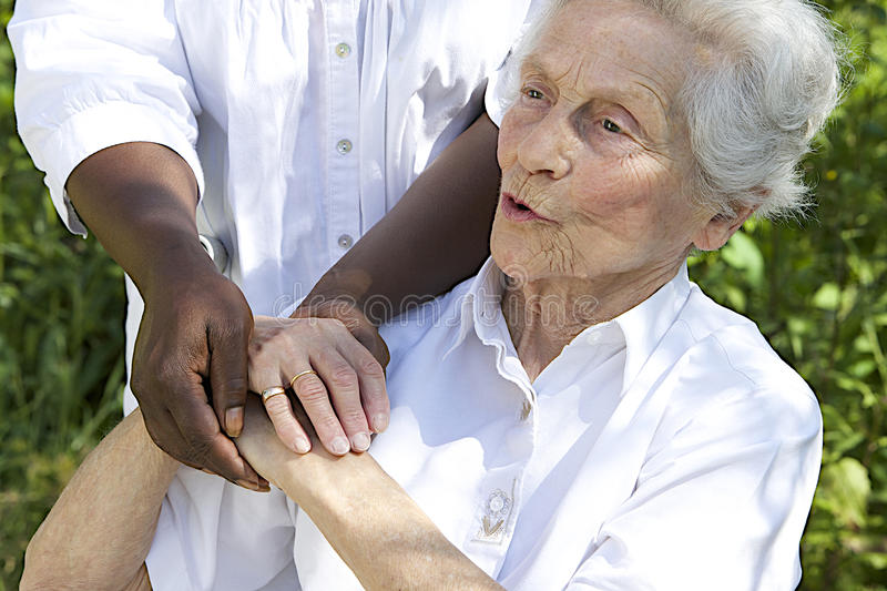 Symbol of comfort and support from a care giver to the Senior. Symbol of comfort and support from care giver to smiling elderly women outdoor royalty free stock image