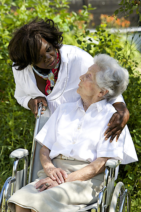 Symbol of comfort and support from a care giver to the Senior. Symbol of comfort and support from care giver talking to elderly women outdoor stock photo