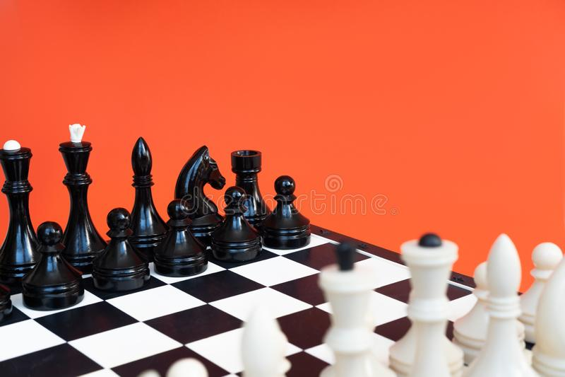 Symbol of competition. Chess board and chess figures on orange background top view copy space. Symbol of competition. Chess board and chess figures on orange royalty free stock image