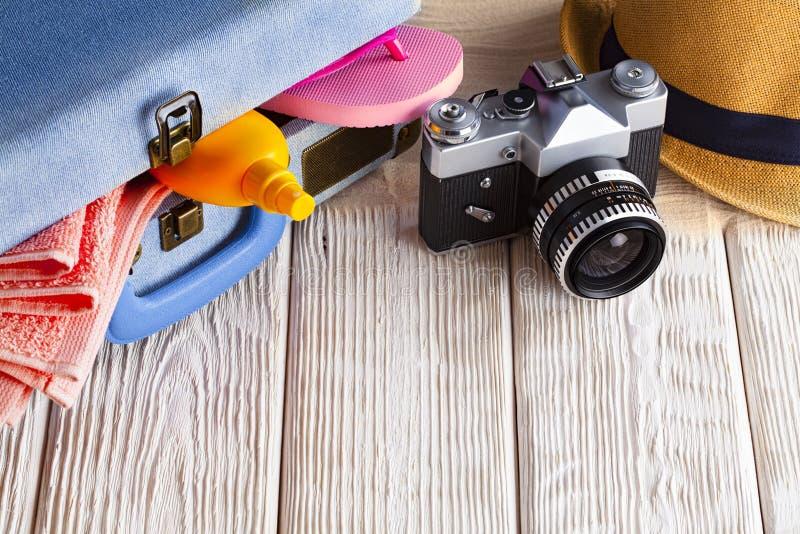 Symbol des Sommerferienrestes - Koffer voll von Gegenständen, von klassischer Fotokamera und von Sommerhut auf hölzernem Hintergr lizenzfreie stockfotografie