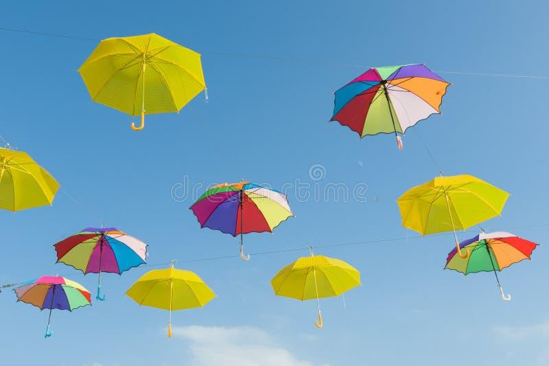 Symbol des Sommers, viele offenen mehrfarbigen Regenschirme auf Himmelhintergrund lizenzfreies stockbild
