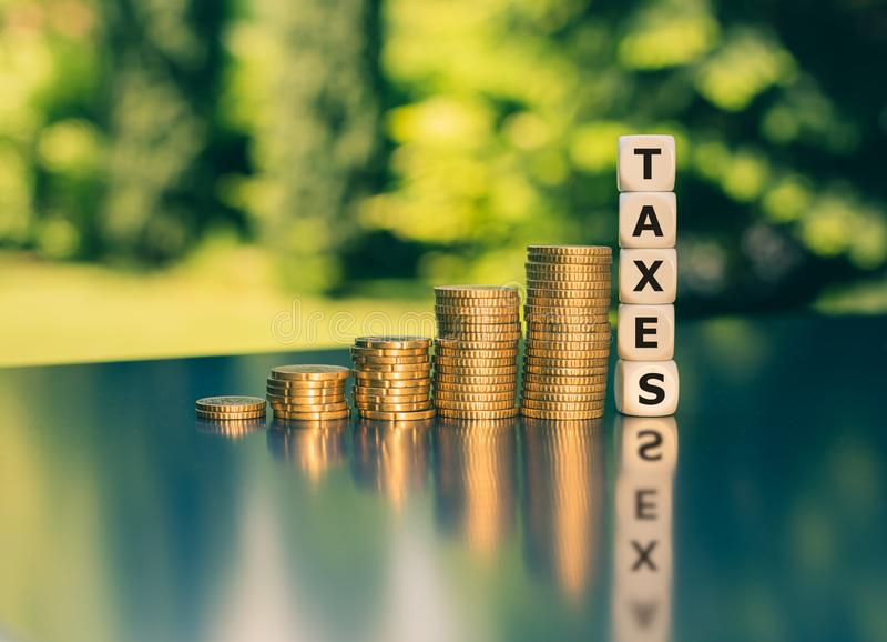 Symbol dla wzrastać podatki Kostki do gry tworzą słowo podatki obok wzrastających wysokich stert monety zdjęcia royalty free