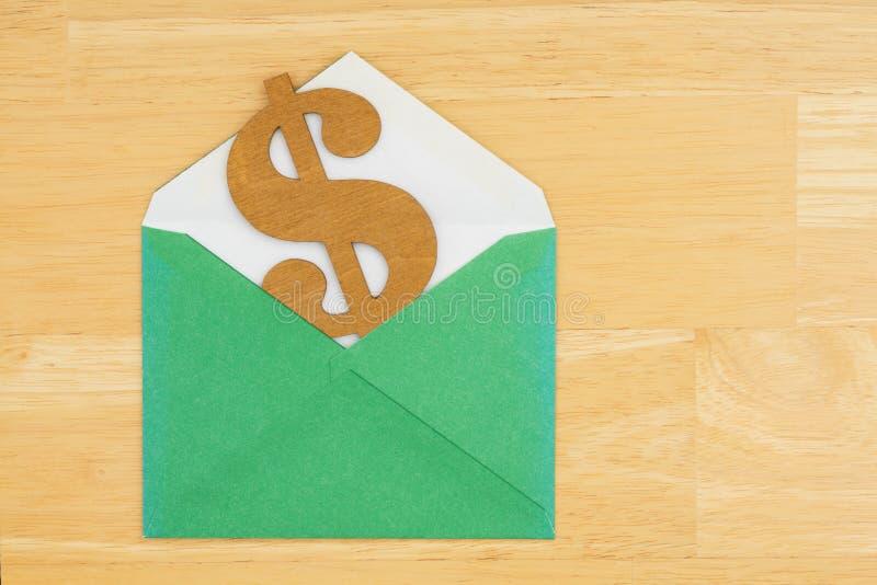 Symbol för dollartecken med det gröna kuvertet på texturerad träbakgrund royaltyfri fotografi