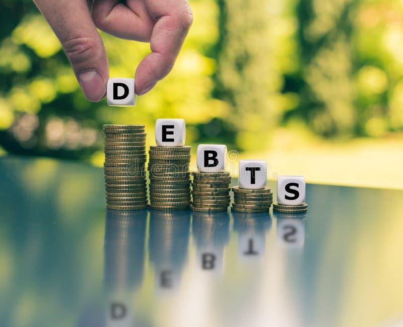 Symbol für abnehmende Schulden Würfel bilden das Wort 'Schulden ' lizenzfreies stockfoto