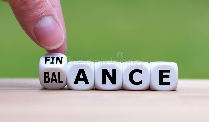 Symbol for finding the right balance in your finance. Hand turns a dice and changes the word `finance` to `balance royalty free stock photos