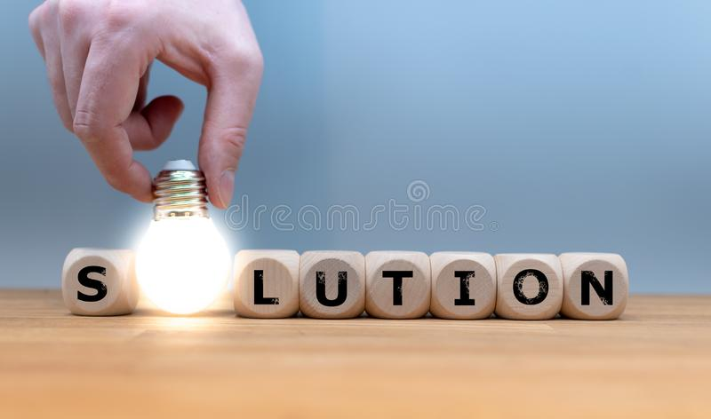 A Symbol for finding a solution. Dice and a light bulb form the word `SOLUTION stock photos