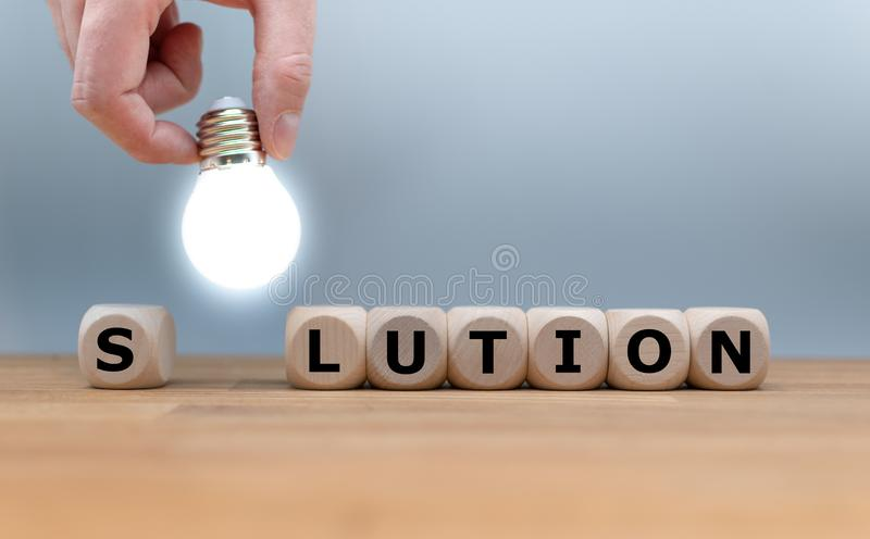 A Symbol for finding a solution. Dice and a light bulb form the word `SOLUTION stock images