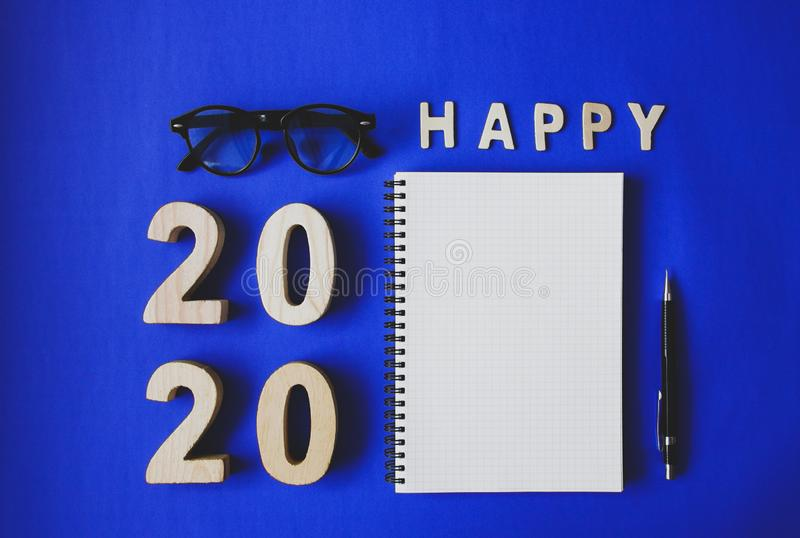 Symbol Happy new year 2020 year, with plywood number 2020, notebook, black vintage glasses and a pencil on blue paper background.  stock images