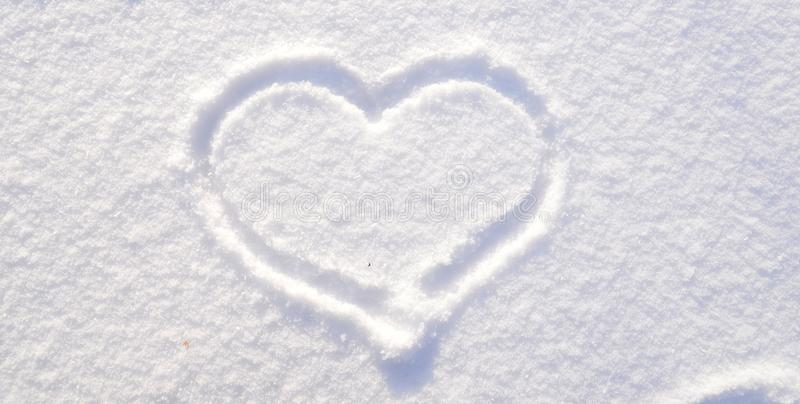 Symbol of heart on the background of fresh snow texture. Merry Christmas or Valentine`s Day Concept. Copy space for your royalty free stock photo