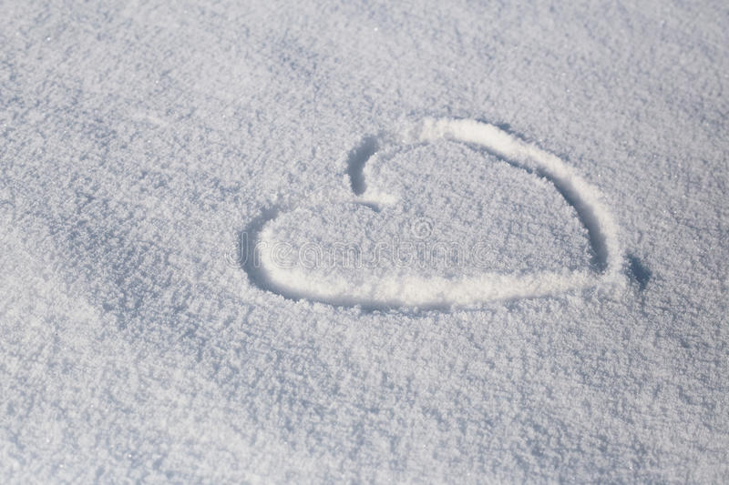 The symbol of the heart painted on the fresh white snow stock photos