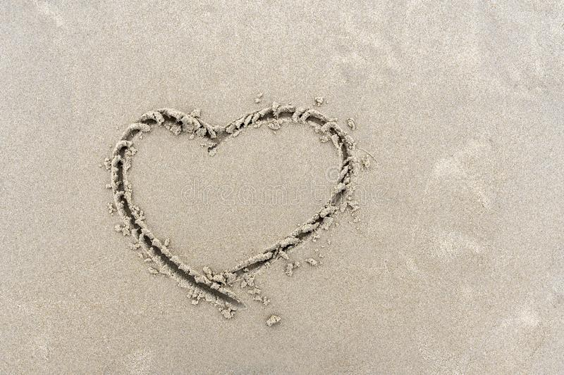 Symbol of heart written by hand on sand of beach stock photos