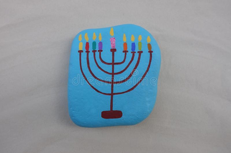 Symbol of jewish holiday Hanukkah with a painted stylized design of a Menorah, candlestick with nine candles over a stone. Cative art work with a stone design stock image
