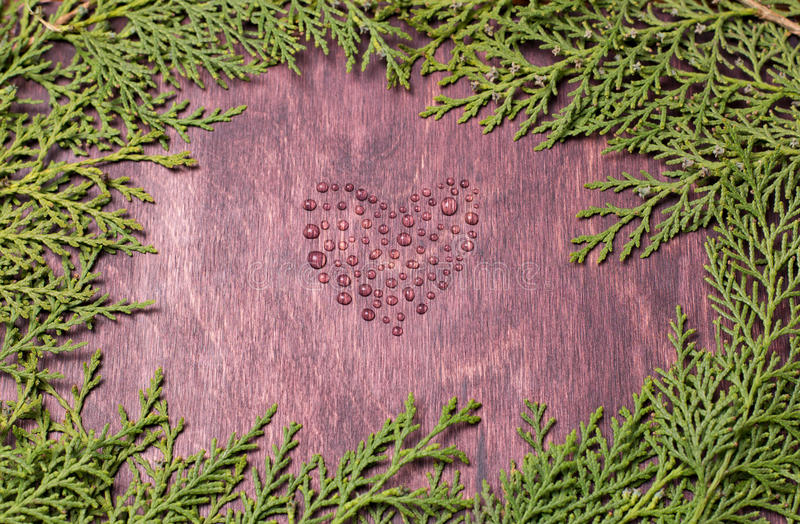 Symbol of love heart from waterdrops on wood wall royalty free stock photo
