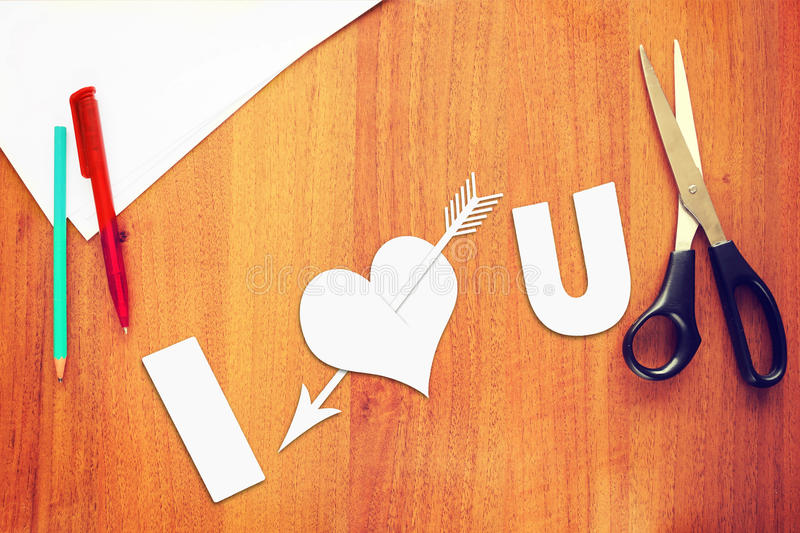 Symbol of love a paper heart pierced by an arrow. On the desk royalty free stock image