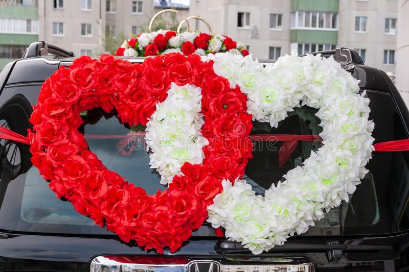 Double hearts of red and white roses on a decorated wedding car, close-up. The symbol of love is Two hearts on the wedding car stock photography