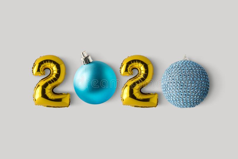 Symbol 2020 made of gold balloons and Christmas decor. Minimal Christmas or New Year concept. Flat lay.  royalty free stock photos