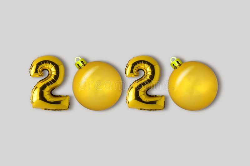 Symbol 2020 made of gold balloons and Christmas decor. Minimal Christmas or New Year concept. Flat lay.  stock image