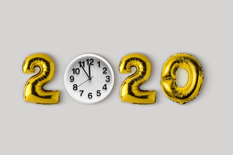 Symbol 2020 made of gold balloons and clock. Minimal Christmas or New Year concept. Flat lay.  royalty free stock images