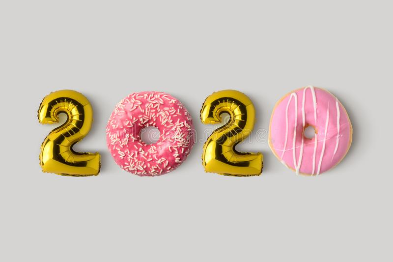 Symbol 2020 made of gold balloons and donuts. Minimal Christmas or New Year concept. Flat lay.  stock photos
