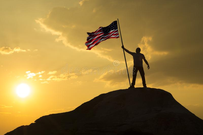 The symbol of a man with the flag of the United States of America stands on the top of the mountain. Against the sky and the sun at sunset. Success and royalty free stock photo