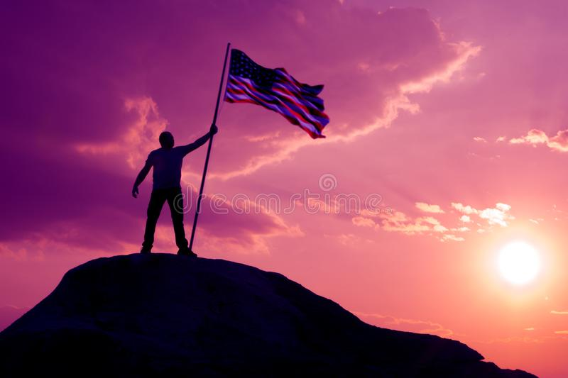 The symbol of a man with the flag of the United States stands on the top of the mountain. Against the sky and the sun at sunset toned the morning in purple stock photography