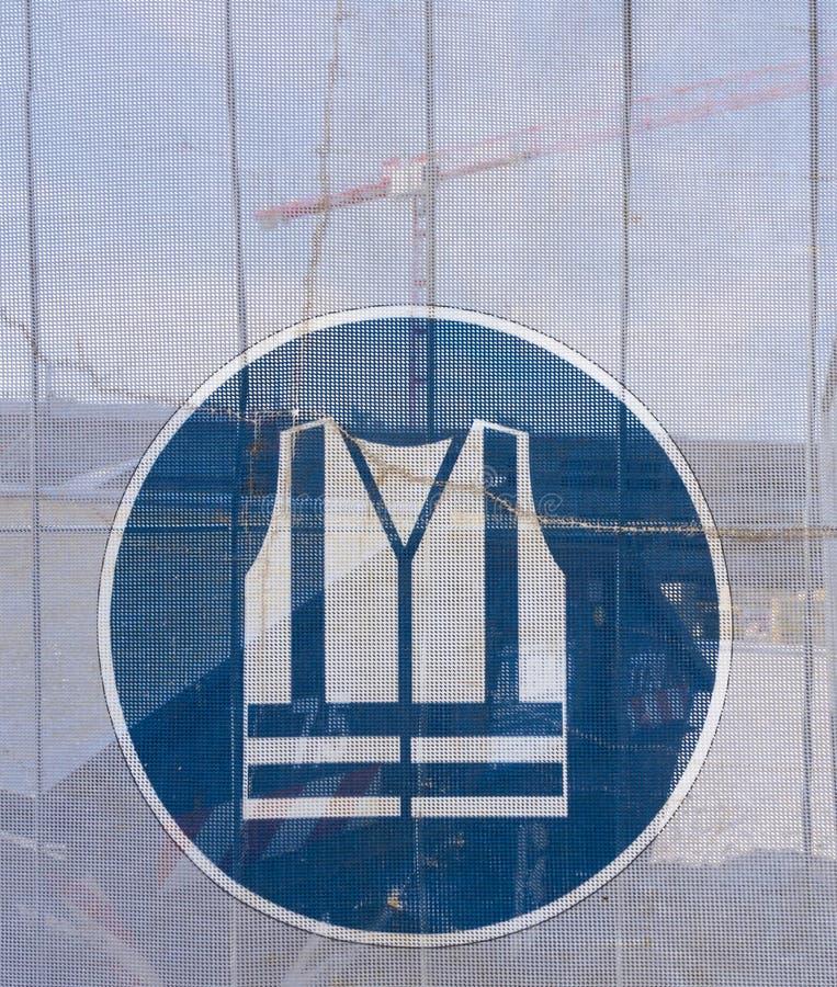 Symbol på en genomskinlig presenning, som delar av jobsiten ses till och med, som en indikering av säkerhet på en konstruktion arkivfoton