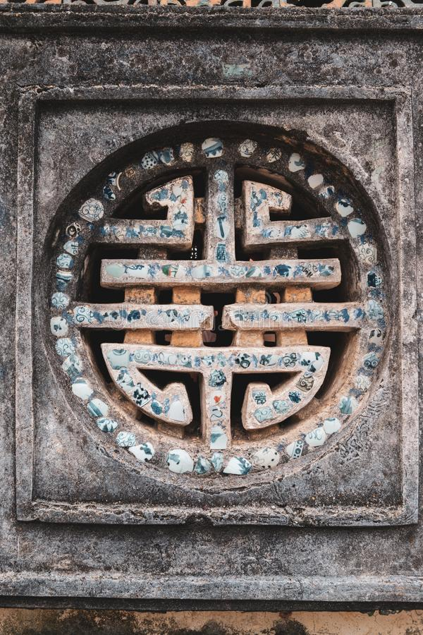 Symbol på en lila vägg i Royal Palace i den forntida imperialistiska staden av tonen, Vietnam royaltyfri fotografi