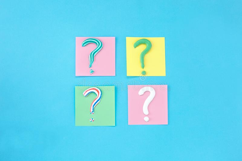 Symbol of question mark from toothpaste on blue background,. Toothpaste selection concept, Concept of dental care. Cleaning teeth stock images