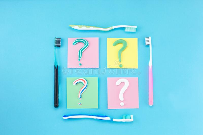 Symbol of question mark from toothpaste and toothbrush on blue background,. Toothpaste selection concept. Concept of dental care. Cleaning teeth royalty free stock image