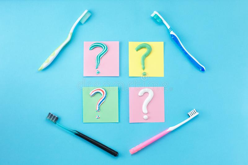 Symbol of question mark from toothpaste and toothbrush on blue background,. Toothpaste selection concept. Concept of dental care. Cleaning teeth royalty free stock photos